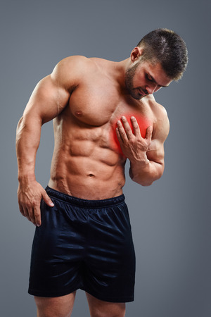 infarct: Muscular shirtless man with chest pain over gray background. Concept with highlighted glowing red spot.