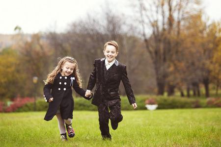 형제와 자매 가을 날 공원에서 실행. 서로의 손을 잡고 어린 소녀와 소년 스톡 콘텐츠