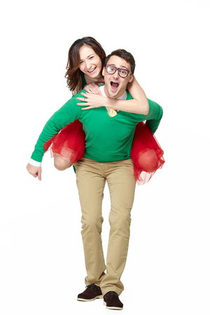 funny guys: Happy young nerds couple. Piggybacking girl on her weird boyfriend isolated on white backgorund Stock Photo