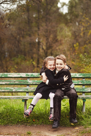 niño y niña: Hermano y hermana abrazos y sentado en un banco en un parque en día de otoño. Niña y niño abrazos Foto de archivo