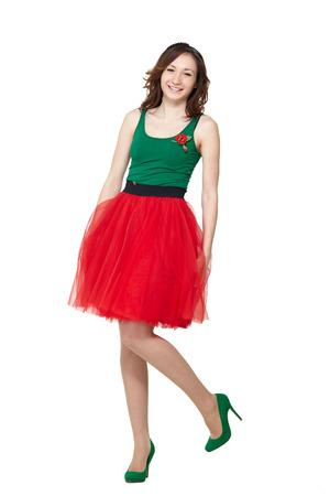 falda: Feliz adolescente falda del verano de la muchacha que desgasta de pie sobre fondo blanco. Modelo sonriente señora bonita morena posando en el estudio