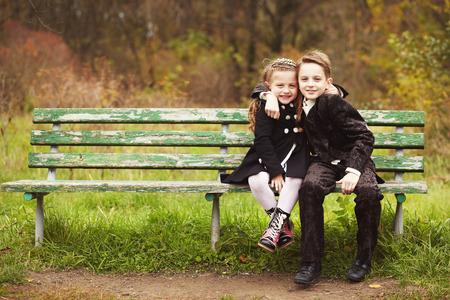 형제 및 자매 껴 안고 및 가을 날 공원에서 벤치에 앉아. 작은 소녀와 소년 포옹