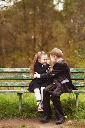 Brother and sister cuddling and sitting on a bench in a park on autumn day. Little girl and boy playing together.