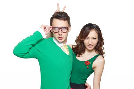 Межрасовые странно ботаник пара. Кавказский молодой человек и Азии женщина обнимает и смотрит уверенно на камеру носить одежду в стиле 50. Пятидесятые концепция ботаник