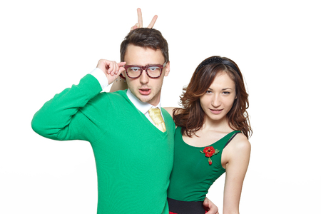 Interracial weird nerd couple. Caucasian young man and asian woman hugging and looking confident at camera wearing 50 style clothes. Fifties nerd concept 版權商用圖片