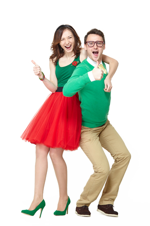 Interracial weird nerd couple showing OK sign. Caucasian young man wearing eyeglasses and smiling asian woman showing thumbs up sign and wearing 50 style clothes. Fifties nerd concept Stock Photo