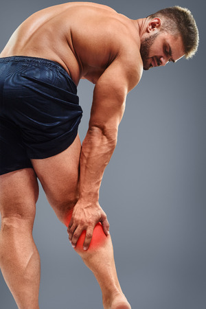 calf pain: Muscle man having calf pain. Bodybuilder tension. Glowing red spot concept