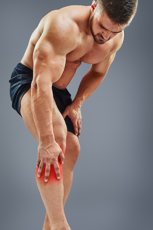 bending: Fit attractive man having a knee pain, bending over the leg, isolated on gray background. Highlighted red spot concept