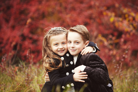 Little pretty girl and young boy huggind each other on autumn day. Brother and little sister cuddling. Happy family Stock Photo