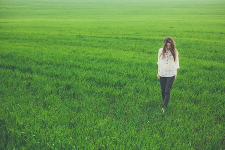 屋外全身緑の野原で悲しい孤独な少女の肖像画。コピー スペースと草原を歩く若い女性。