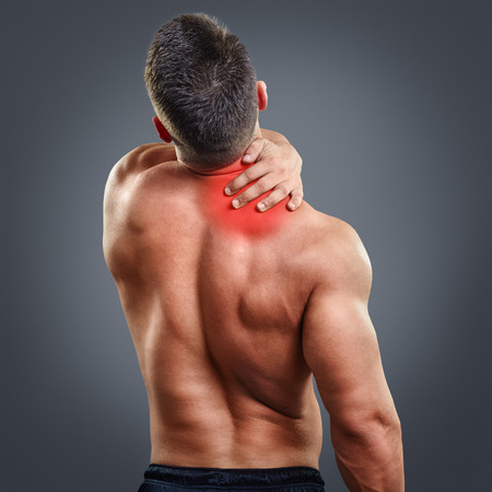 Back view portrait of a man with neck pain over gray background. Concept with highlighted glowing red spot.