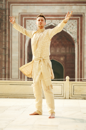 kurta: Confident young man with open arms wearing kurta, standing barefooted in Taj Mahal, India.