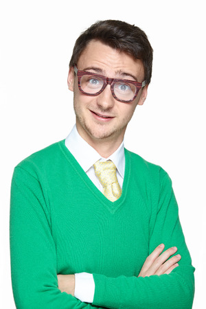 arms crossed: Portrait of smiling weird young man wearing big eyeglasses and holding arms crossed isolated on white background. Surprised nerd. Stock Photo