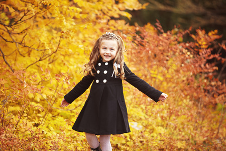 warm clothing: Fashion little girl wearing a cute coat on autumn day. Cheerful child on a yellow leaves background