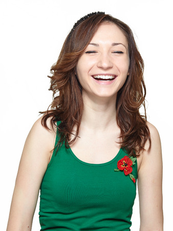 Happy teenager girl laughing isolated on white background,. Cheerful asian young woman  wearing green sleeveless t-shirt and smiling Фото со стока
