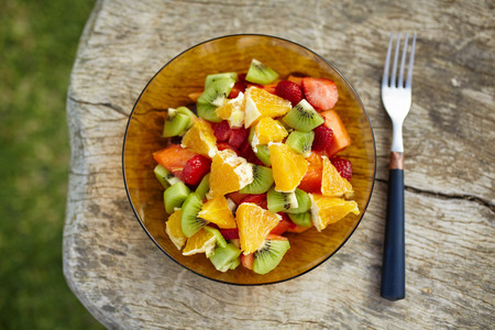 sweet food: Bowl of healthy fresh fruit salad with oranges, strawberries, kiwi and papaya on wooden background. Closeup top view. Stock Photo