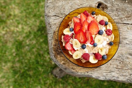 yogur: Yogur, cereales y copos de ma�z con bayas frescas y pl�tano con espacio de copia. Vista superior. Foto de archivo