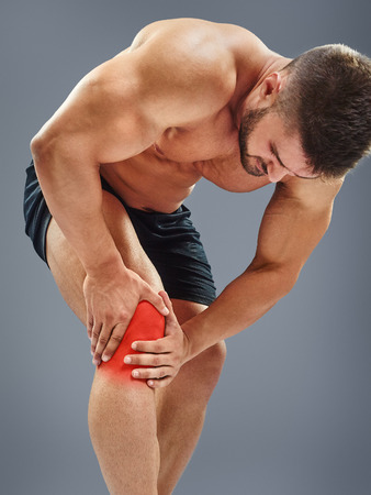 gripping: Bodybuilder gripping an inflamed knee, isolated on gray background. Highlighted red spot concept Stock Photo