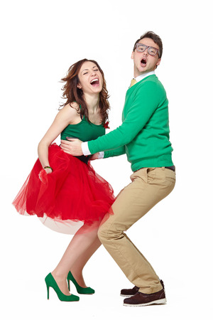 Interracial weird nerd couple dancing together. Caucasian young man wearing eyeglasses and smiling asian woman screaming and wearing 50 style clothes. Fifties nerd concept Stock Photo