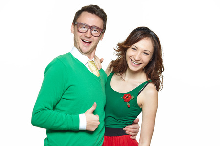 two face: Interracial weird nerd couple showing OK sign. Caucasian young man wearing eyeglasses and smiling asian woman showing thumbs up sign and wearing 50 style clothes. Fifties nerd concept Stock Photo
