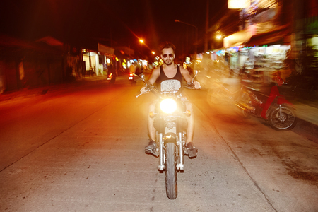 Front view of young man biker riding a motorcycle in night city. Long exposure. High speed driving.