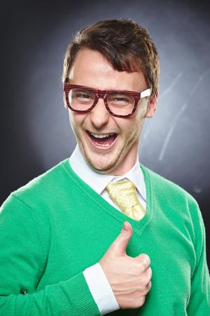 Nerd usando óculos que mostram os polegares acima do sinal. Homem de sorriso novo que mostra o gesto aprovado.