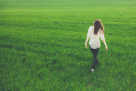 rear view girl: Unrecognizable lonely sad girl walking on summer meadow. Rear view. Sadness and loneliness concept with copy space. Stock Photo