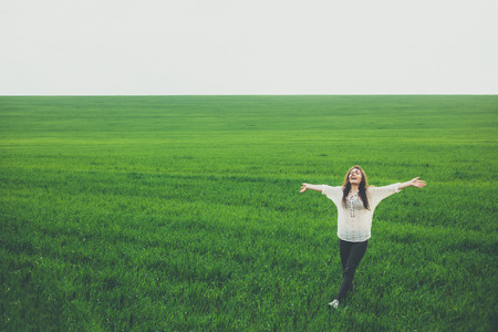 緑の野原を歩いて幸せな若い女。腕コピー スペースと草原の真ん中で調達して立っているきれいな女の子。自由、幸福、自然、夏のコンセプト。