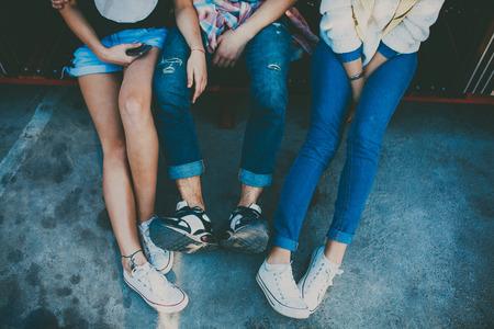 Ноги трех друзей сидели. Обрезанные портрет двух девочка и один мальчик расслабляющий. Вид сверху на брюки в обтяжку обувь отдыхая.