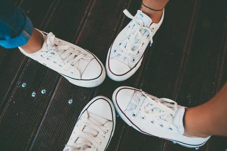 Крупным планом битник обуви. Лучшие друзей носить ту же белую обувь. Белые кроссовки на деревянный пол Фото со стока