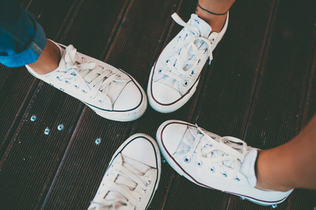 Closeup of hipster shoes. Best friends wearing same white footwear. White sneakers over wooden floor