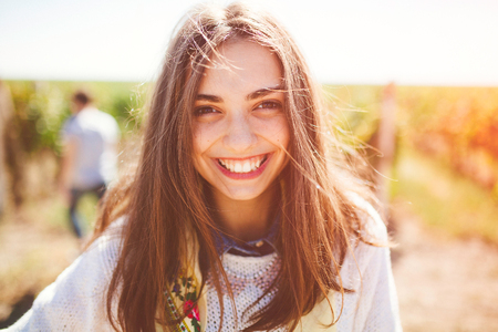 Smiling teenage girl outdoors on sunny day. Closeup of cute brunette young woman wearing casual clothes.