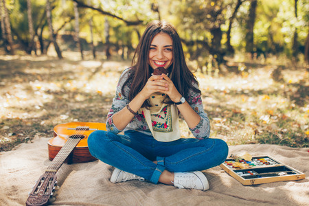 Adorable teenager girl wearing casual clothes having a picnic on autumn day in forest. Cute and beautiful hipster young woman smiling and holding a cupcake, sitting on blanket by guitar.