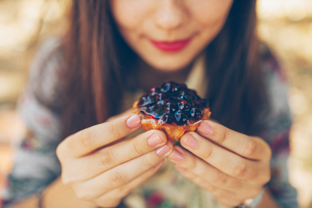 Closeup of girl holding berries tartalet. Young woman hands close up with currant little cake and defocused background