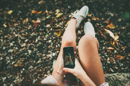 10 代の少女は、石の多い湖畔に白い靴を履いて足の selfie 写真を撮るします。