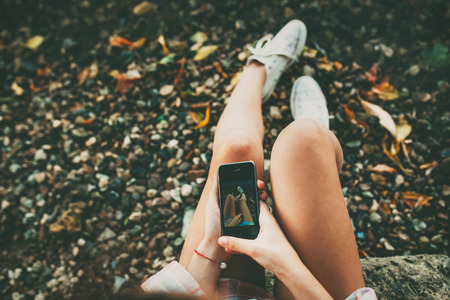 Teenage girl taking a selfie picture of her feet wearing white shoes on stony lakeside. Stock Photo