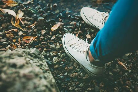 Крупным планом белые туфли обувь на скалистом фоне.