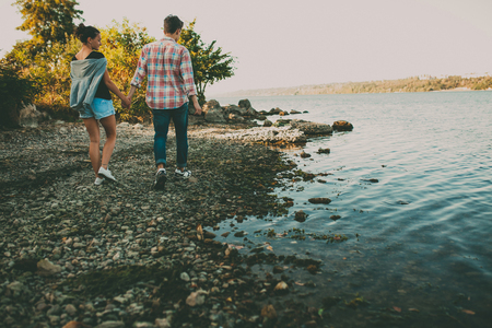 a pair of: Teenage loving couple walking together by lake. Handsome teen hipster boy and girl holding hands. Back view.