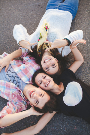 Three happy teenage friends lying together and laughing. Top view. Best friends. 版權商用圖片