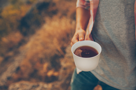 Closeup of white cup with tea. Young man holding a cup with coffee outdoors. Mug design concept.