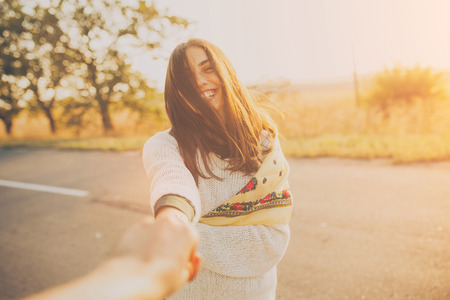 Primeira pessoa retrato de uma menina sorridente segurando a mão no por do sol. Mulher nova adorável no dia ensolarado