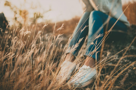 Расфокусированным абстрактное понятие одиночества. Обрезанные ноги одинокой молодой женщины, сидя на камне. Одиночество