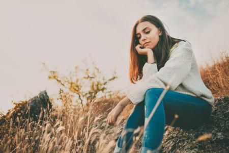 soledad: Adolescente sentado solo en el día de otoño frío. Mujer sola triste joven vistiendo pensamiento suéter caliente y dudando. La soledad y el concepto de la soledad.