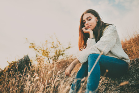 one teenager: Teenage girl sitting alone on autumn cold day. Lonely sad young woman wearing warm sweater thinking and hesitating. Loneliness and solitude concept.