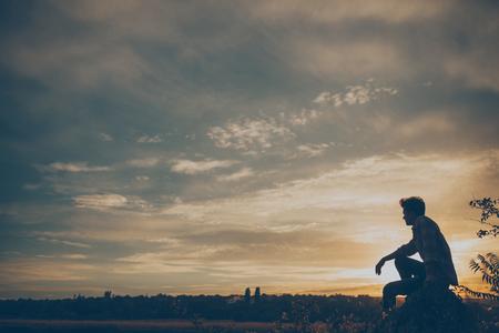 夕日や日の出に座っている若い男のシルエット。崖石に自信を持っている 10 代の少年 thinkig。願ってください。悲しみ。自由。