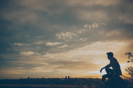 Silhueta do homem novo que senta-se no por do sol ou nascer do sol. Confiantes thinkig adolescente na pedra penhasco. Esperan Banco de Imagens