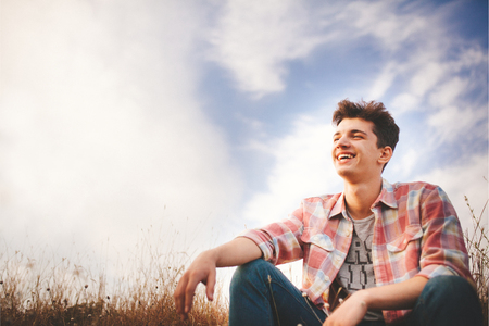 laughing face: Handsome teenager boy wearing casual shirt. Happy smiling young man sitting on grass on sky background