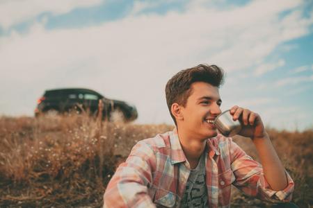 uomo felice: Fiducioso ragazzo sorridente seduta all'aperto con la sua auto SUV su sfondo e bere il t�