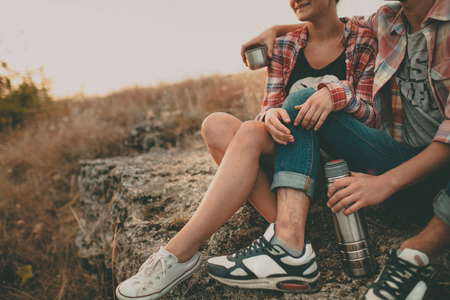 young love: Cropped shot of young man and woman sitting on a stone with thermos. Teenagers loving couple wearing casual clothes relaxing outdoors