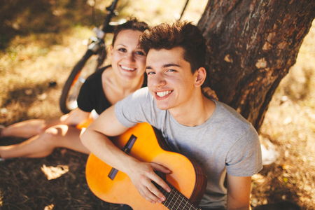 Teenage smiling loving couple with guitar sitting by a tree, having a picnic in forest on autumn day. Handsome teen hipster boy and girl spending weekend and playing guitar